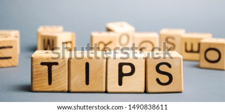 Wooden blocks with the word Tips and randomly scattered cubes. Award for good service in the cafe restaurant. A gratuity is a sum of money customarily given by a client or customer to a service worker #1490838611
