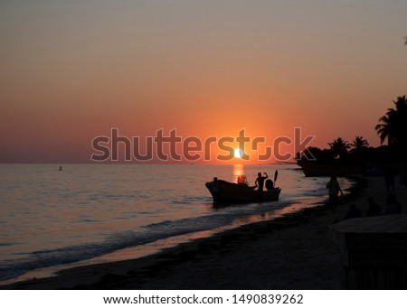 Sunset over the Mozambique Channel taken from a beach near Tulear, south west madagascar.  Silhouetts of boat and people,  #1490839262