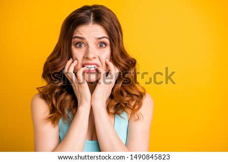 Photo of terrible feared girlfriend driven mad with some sorrow happened to her biting nails with panic while wearing teal tank-top isolated with yellow vivid color background #1490845823