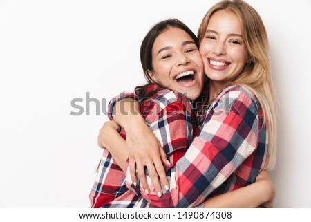Image of a smiling happy young pretty girls friends sisters posing isolated over white wall background hugging.