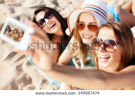 summer holidays, technology and beach concept - girls taking selfie on the beach