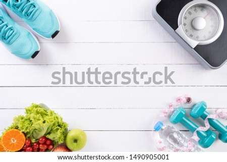 Healthy lifestyle, food and sport concept. Top view of athlete's equipment Weight Scale measuring tape blue dumbbell, sport water bottles, fruit and vegetables on white wooden background. #1490905001