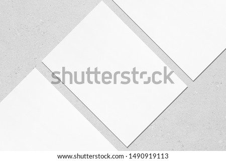 Closeup of three empty white rectangle poster mockups lying diagonally with soft shadow on neutral light grey concrete background. Flat lay, top view. Open composition. #1490919113