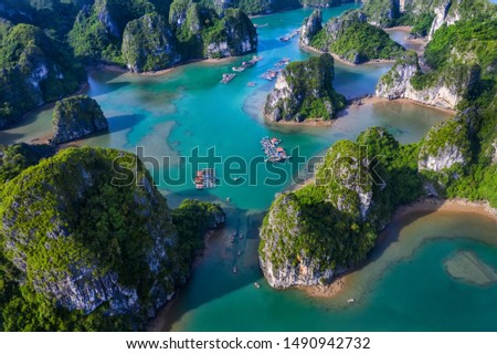 Aerial view Vung Vieng floating fishing village and rock island, Halong Bay, Vietnam, Southeast Asia. UNESCO World Heritage Site. Junk boat cruise to Ha Long Bay. Famous destination of Vietnam Royalty-Free Stock Photo #1490942732