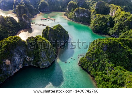 Aerial view of tourists on the boat in Vung Vieng floating fishing village and rock island, Halong Bay, Vietnam, Southeast Asia. UNESCO World Heritage Site. Junk boat cruise to Ha Long Bay. Royalty-Free Stock Photo #1490942768