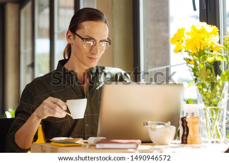 Energizing drink. Pleasant long haired man holding a cup with espresso while looking at the laptop screen #1490946572