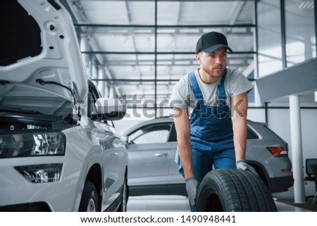 Not that hard. Mechanic holding a tire at the repair garage. Replacement of winter and summer tires. #1490948441