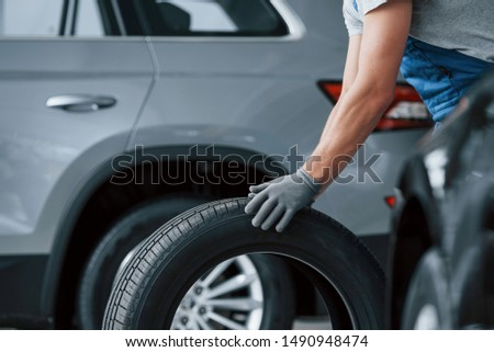Grey shirt. Mechanic holding a tire at the repair garage. Replacement of winter and summer tires. #1490948474