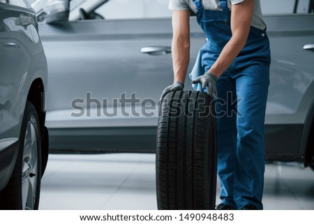Process of maintenance. Mechanic holding a tire at the repair garage. Replacement of winter and summer tires. #1490948483