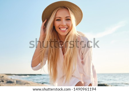 Young attractive smiling blond woman in white shirt and hat joyfully looking in camera with sea on background #1490961194