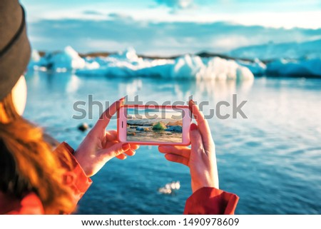 girl taking a picture of a blue iceberg in ice lagoon at Iceland