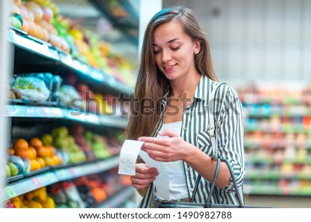 Young woman with shopping basket checks and examines a sales receipt after purchasing food in a grocery store. Customer buying products at supermarket  Royalty-Free Stock Photo #1490982788