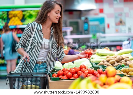 Woman with shopping basket chooses and purchases fresh ripe organic tomatoes in vegetable department of supermarket. Customer buying food at grocery store #1490982800