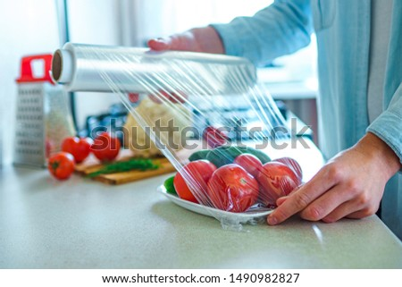 Woman packaged fresh vegetables using food film for food storage Royalty-Free Stock Photo #1490982827