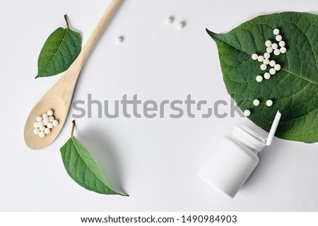 Homeopathy, naturopathy and alternative herbal medicine. Bottle with homeopathic pills on green plant leaf. Top view, flat lay with copy space over white background #1490984903