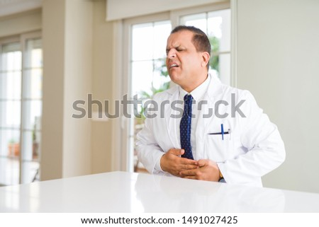 Middle age doctor man wearing medical coat at the clinic with hand on stomach because indigestion, painful illness feeling unwell. Ache concept. #1491027425