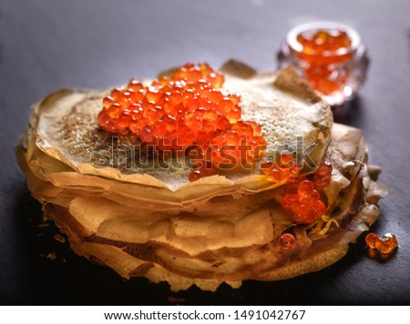 Round blinzes blinis with red caviar  Royalty-Free Stock Photo #1491042767