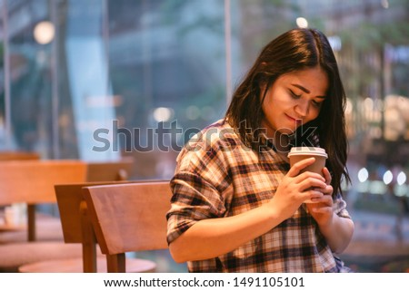 Asian women wearing brown striped shirts Hold a cup of coffee while relaxing in the coffee shop. drinks and people concept #1491105101