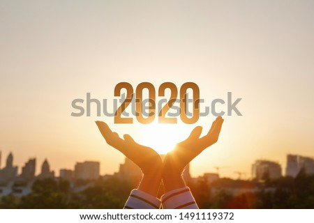 The concept new 2020 year. Hands show 2020 on the background of sunset. #1491119372