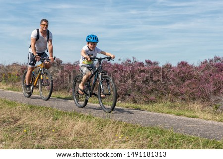 Ermelo, The Netherlands - August 23, 2019: Man and boy at mountain bikes cycling through blooming purple heath in Dutch National Park Veluwe #1491181313