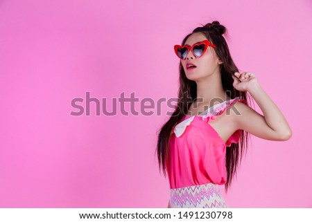 A beautiful woman wearing red glasses with a big hat on a pink background. #1491230798