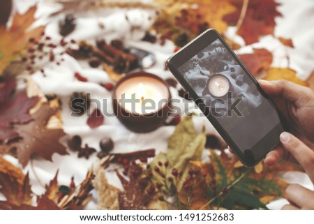 Autumn hygge flat lay. Hand holding phone and taking photo of candle, berries, fall leaves, anise,herbs, acorns, nuts, cinnamon, cotton on white textile. Hygge lifestyle, cozy autumn mood