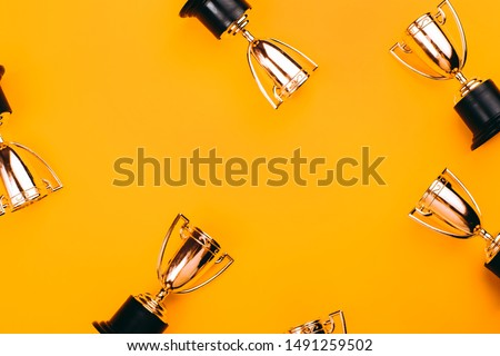 Winner or champion cup on bright background, Flat lay style. Open composition. Royalty-Free Stock Photo #1491259502