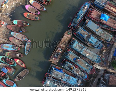 fishing boats leaning on a small dock. Maritime industry in Indonesia. River as the exit and entry of fishing boats seen from above with aerial drone camera #1491273563