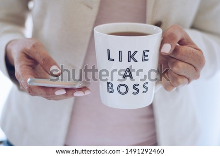 Professional woman using mobile phone and holding a cup that says LIKE A BOSS #1491292460