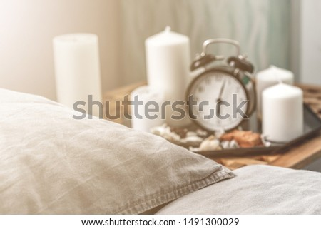 Cozy grey bedroom interior with comfortable bed near the wooden night table with candle, alarm clock and dried flowers. Cozy atmosphere at home. Warming up the cold winter or autumn evenings.  #1491300029