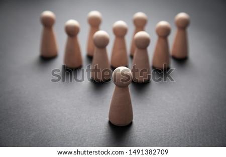 Wooden human figures on the black background. Leader #1491382709