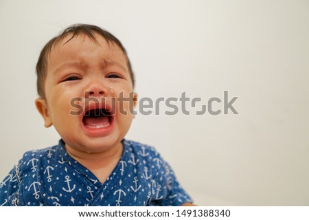 An asian looking little boy unhappy facial expressions, and crying inconsolably. #1491388340