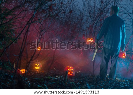 scary man in night  forest is cutting Halloween pumpkins #1491393113