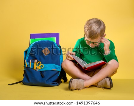 Children go back to school. Stylish boy doing homework at home with backpack full of books, pencils. Pupil reading a book, writing and painting. Kid is drawing. Child in glasses on yellow wall. #1491397646