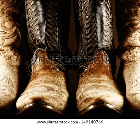 High contrast photo of several pair of worn cowboy boots, with center pair being a matched pair. #149140766