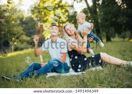 Young happy family of three having fun together outdoor.  #1491496349