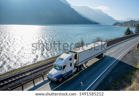 Big rig classic American powerful white semi truck with refrigerated semi trailer transporting frozen goods running on the road along railroad and river in Columbia Gorge area with mountain ranges #1491585212
