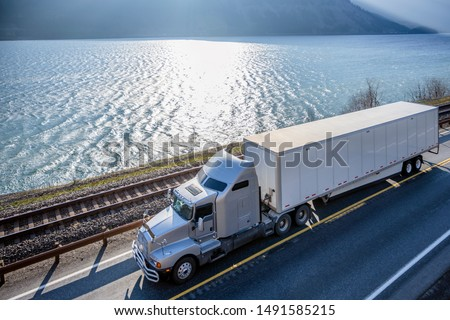 Big rig classic American powerful gray semi truck with dry van semi trailer transporting commercial cargo running on the road along railroad and river in Columbia Gorge area with mountain ranges #1491585215