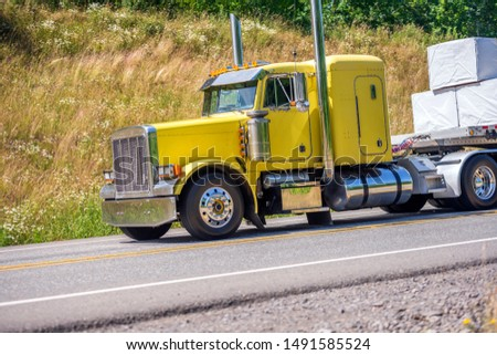 Big rig yellow classic long haul semi truck with flat bed semi trailer transporting tightened packed lumber boards running downhill on the turning winding road with hills and trees in sunny day #1491585524