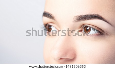 Woman with beautiful eyebrows close-up on a light background with copy space. Microblading, microshading, eyebrow tattoo, henna, powder brows concept. #1491606353
