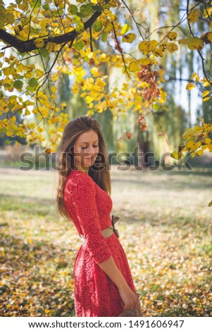 Beautiful girl in a red dress in a park. Autumn concept. #1491606947