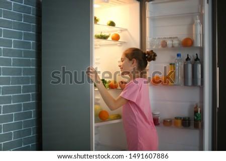 Girl choosing food from fridge late at night #1491607886