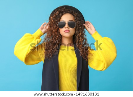 Stylish African-American woman on color background #1491630131