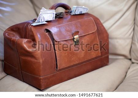 Old vintage red leather case full of money coming out of the sides. Scratched bag on leather sofa, business, bribe or prize concept. Indoors, copy space. #1491677621