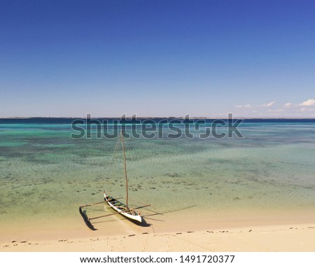 Aerial view of traditional dugout Vezo pirogue with outrigger on a coral sand beach at Nosy Hao island, on the barrier reef, with  Madagascar on the horizon #1491720377