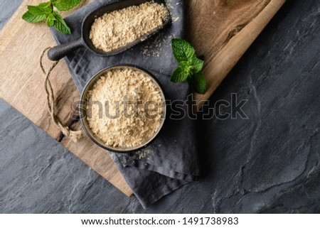 Dietary supplement, Maca root powder in a bowl and scoop on stone background with copy space #1491738983