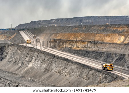 Coal mine, aerial view. Road for the movement of mining trucks. Ways to transport minerals to the surface of the earth. A mining truck is driving along a mountain road. #1491741479