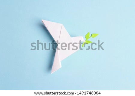 Paper origami dove of peace with olive branch on a blue background. World Peace Day concept. #1491748004
