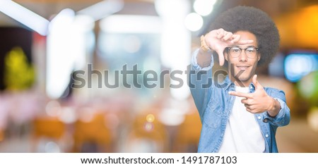 Young african american man with afro hair wearing glasses smiling making frame with hands and fingers with happy face. Creativity and photography concept. #1491787103