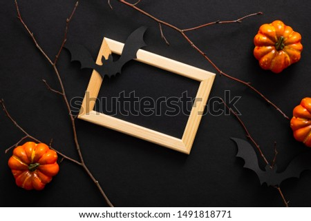 Halloween decorations, pumpkins, bats,  picture frame on black background. Halloween concept. Flat lay, top view, overhead.